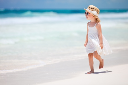 woman beach dress: Adorable little girl walking along white sand Caribbean beach