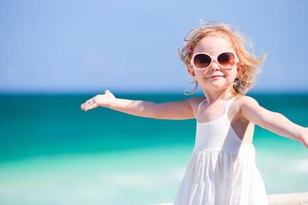arena: Adorable niña pequeña sonriente feliz de vacaciones de playa