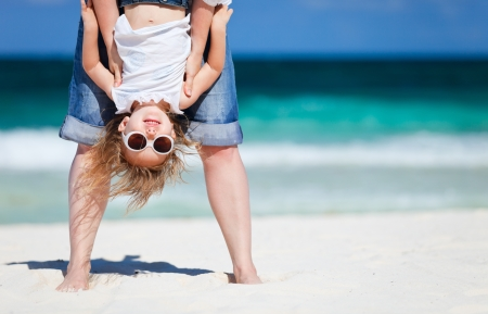 Mother holding her happy smiling daughter upside down having beach fun photo