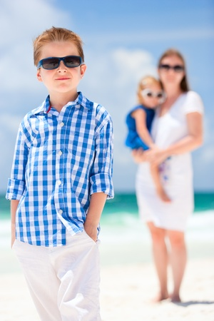 Cute little boy portrait at beach with his family on background photo