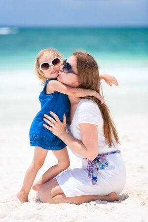 Young mother kissing her little daughter photo