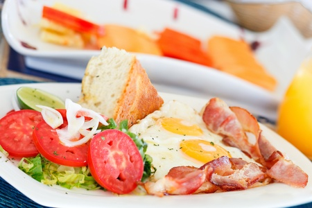 Delicious fried eggs with bacon and vegetables served for breakfast photo
