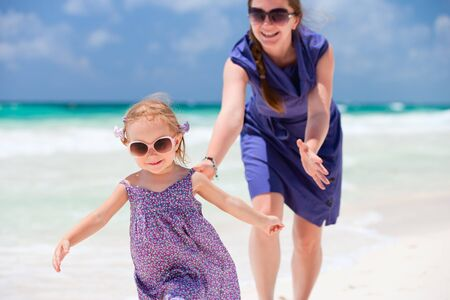 Mother and her little daughter running at tropical beach Stock Photo - 9773596