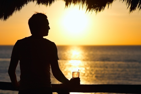 Silhouette of young man having drink at sunset Stock Photo - 9773595