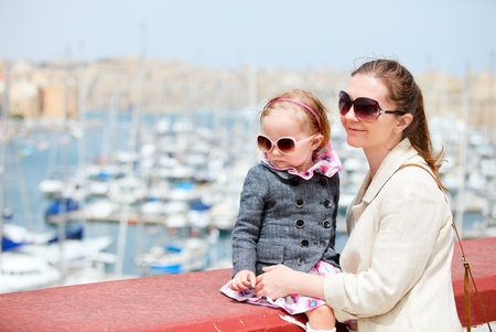 Mother and her little daughter outdoors in city near harbor Stock Photo - 9784325