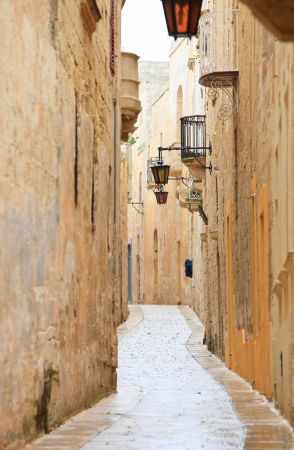 Narrow medieval stone paved street in Mdina the former capital of Malta