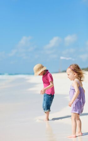 Brother and sister together on tropical beach photo