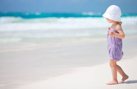 klein meisje op strand: Schattig meisje met lolly op witte zand Caribische strand Stockfoto