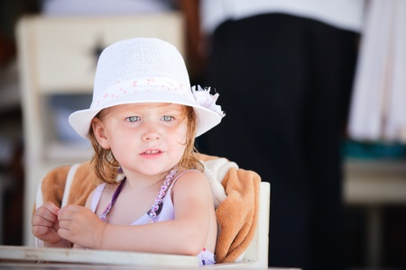 Casual portrait of adorable little girl sitting at beach restaurant Stock Photo - 9784298