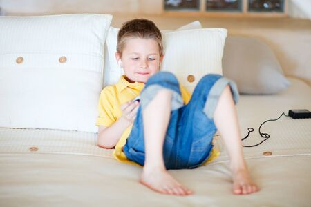 Little boy playing video games on portable console or mobile phone photo