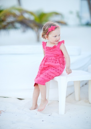 woman beach dress: Portrait of adorable little girl sitting at white sand beach Stock Photo