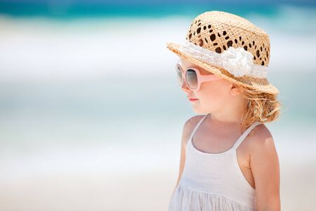 glasses in the sand: Portrait of adorable little girl wearing elegant hat Stock Photo