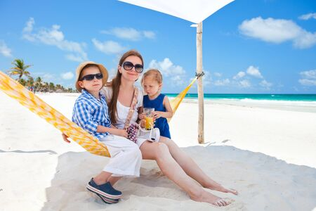 Mother and two kids sitting on hammock at tropical beach photo