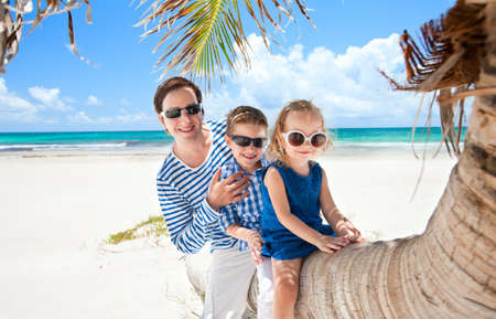 Father and two kids sitting on palm at Caribbean beach photo