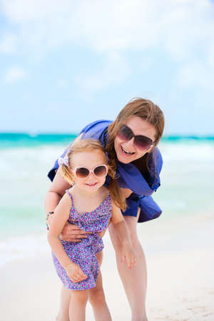 Happy mother and daughter having fun at beach Stock Photo - 9784286