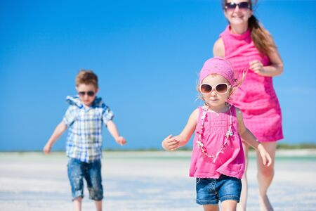 Happy mother and her kids running at tropical beach photo