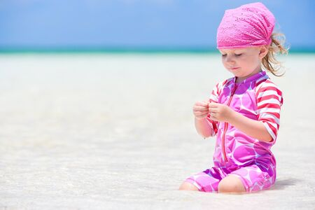 Adorable toddler girl at tropical beach playing in shallow water photo