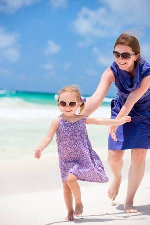 Mother and her little daughter running at tropical beach photo