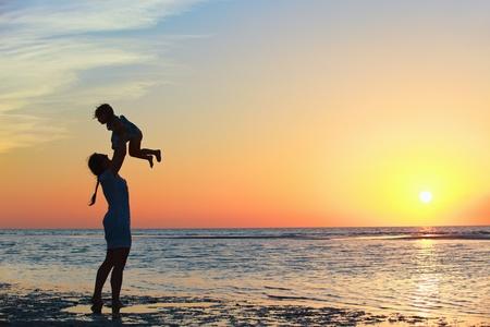 母と夕暮れ時のビーチで小さな娘シルエット