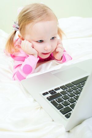 Wide lens shot of adorable little girl with laptop  photo