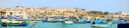 Panorama of Marsaxlokk village and traditional colorful boats in Malta photo