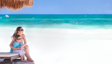 Panoramic photo of mother and son at tropical beach in Tulum Mexico photo