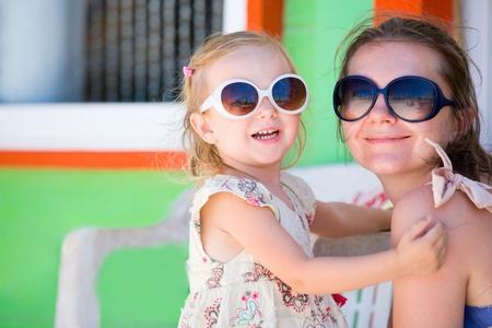 Mother and daughter portrait with colorful Caribbean house on background photo
