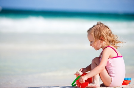 Adorable little girl playing with beach toys on white sand beach photo
