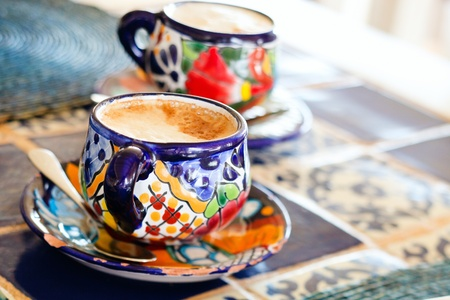 Cappuccino in traditional colorful mexican pottery cups Stock Photo