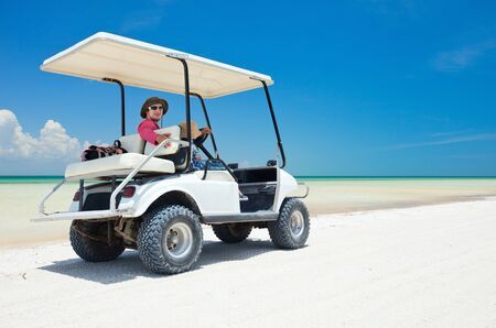 golf cart: Family driving in golf cart along the tropical beach