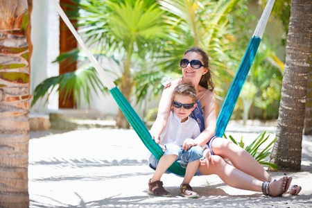 Mother and son on tropical vacation relaxing in hammock photo