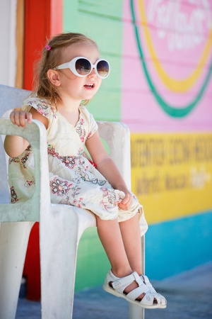 Little girl portrait with colorful Caribbean house on background Stock Photo - 9978491