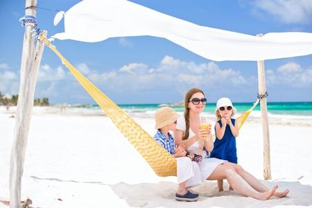 klein meisje op strand: Moeder en twee kinderen zitten op hangmat op tropisch strand Stockfoto
