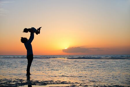 father daughter: Father and little daughter silhouettes on beach at sunset Stock Photo