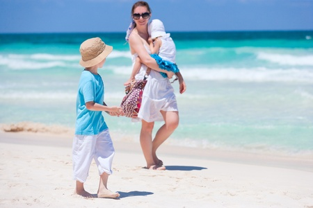 Mother and two kids walking along tropical beach Stock Photo - 10084231