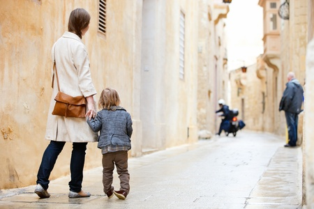 autumn in the city: Back view of mother and her little daughter outdoors in city Stock Photo