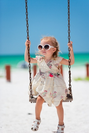 Little girl swinging with tropical beach on background photo