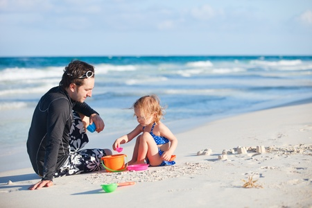father and daughter: Cha và con gái chơi với đồ chơi ở bãi biển