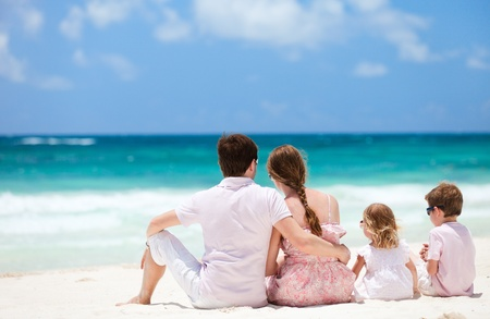 Family of four sitting on Caribbean beach photo