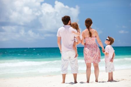 Family of four sitting on Caribbean beach photo