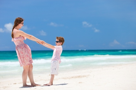 Happy mother and son at tropical beach having fun photo
