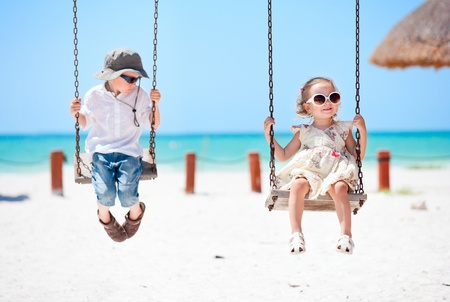Little kids swinging with tropical beach on background photo