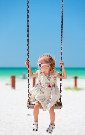Little girl swinging with tropical beach on background Stock Photo