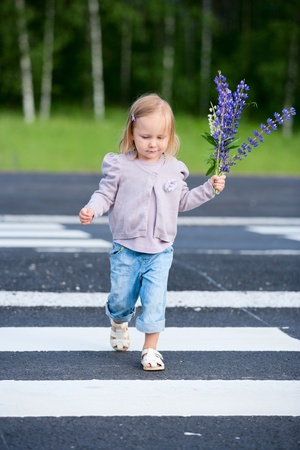 one little girl: Little girl crossing road with flowers in one hand