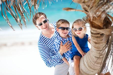 petit homme: P�re et deux enfants assis sur palm Beach Cara�bes