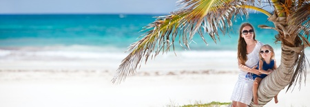 Panoramic photo of mother and daughter sitting on palm at Caribbean beach photo