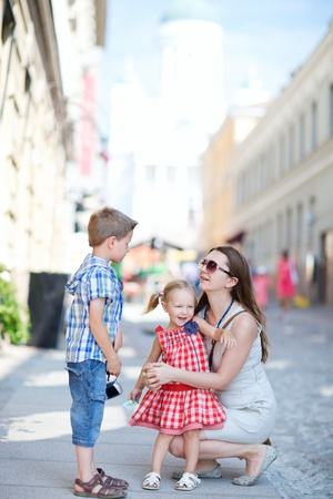 Young beautiful woman with her two kids in city at summer day Stock Photo - 10345068