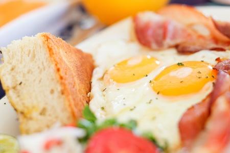 huevos fritos: Deliciosos huevos fritos con tocino y verduras que se sirven en el desayuno
