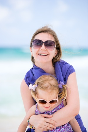 Happy mother and daughter having fun at beach photo