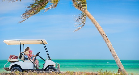 Family driving golf cart along the tropical beach photo